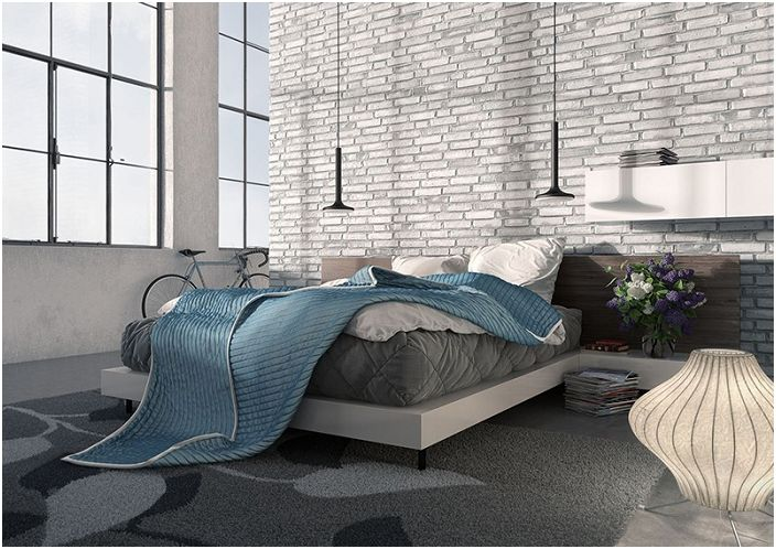 Спалнята с висок таван е наводнена с естествена светлина в сиви и бели тонове.