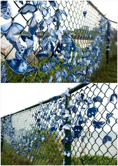 Забор, украшенный тканевыми бабочками.