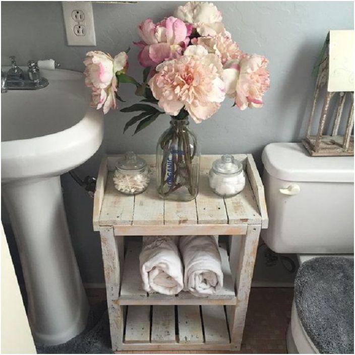 Стара маса за баня, украсена със стъклена бутилка с изкуствени цветя.
