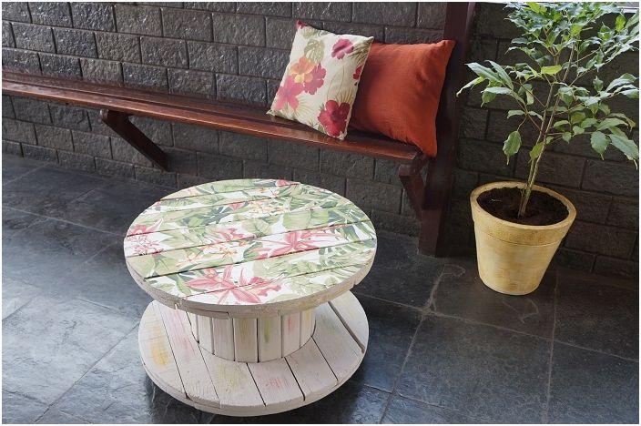 Интересный дизайн стола-катушки с прекрасным принтом с изображением цветов.