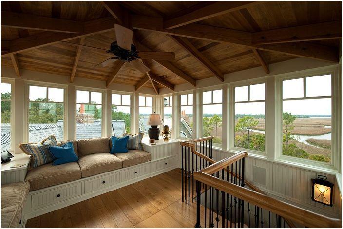 Отличен диван до прозореца под покрива на къщата, който ще се превърне в любимо място за почивка.