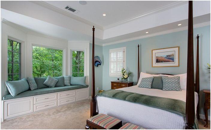 За да спестите място в спалнята, можете да създадете уютна седалка на прозореца на перваза на прозореца.