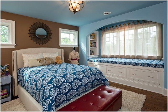 Интересен дизайн на стаята в сини тонове със седалка на прозореца, която украсява цялостната картина на стаята.