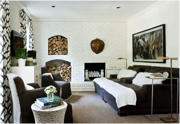 Удобная мебель и белоснежная каменная стена - отличительные черты этой гостиной.