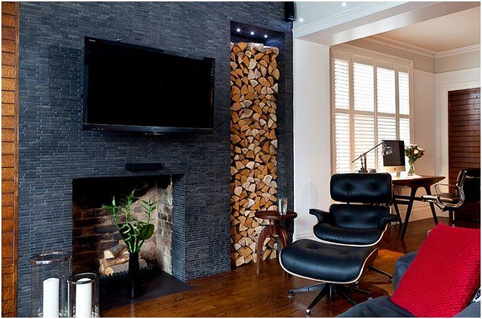 Гостиная в темных цветах украшена местом для хранения дров, что создает своеобразную атмосферу.