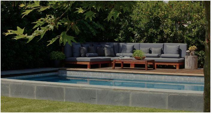 Отлична декорация на мястото до басейна с удобен сив диван, разположен там.
