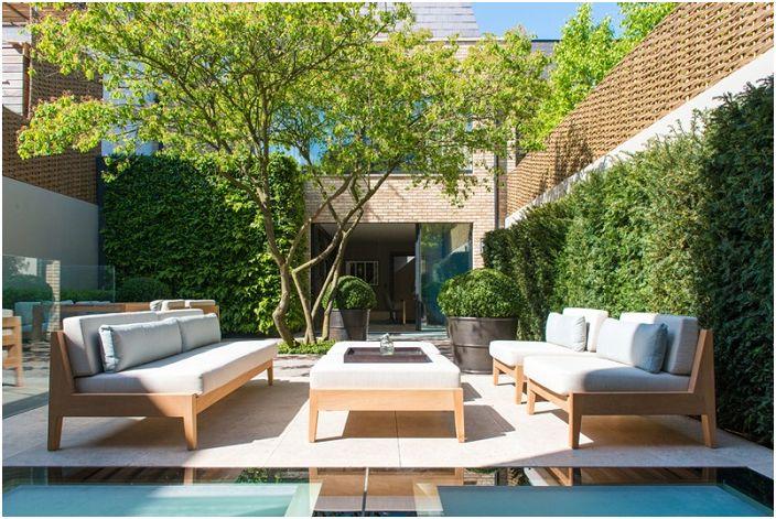 Уютното подреждане на дивани един срещу друг ще създаде уютна атмосфера на улицата в близост до къщата.