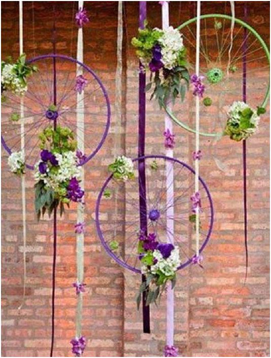 Хубава композиция от цветя, която се допълва от колела по свой начин, какво е необходимо за интересен интериор.