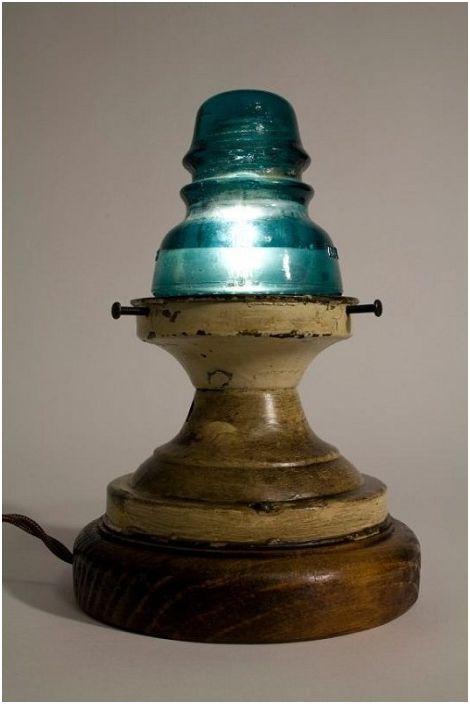 Дървената основа и стъкленият електрически изолатор образуват настолна лампа.