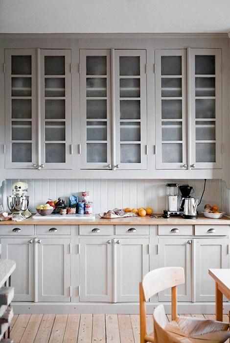 Светло-серый шкаф с тонированными стеклами выглядит очень симпатично и практично.