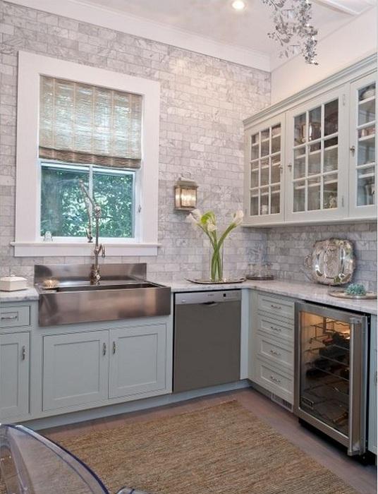 Интересная кухня с симпатичными светлыми шкафами и мраморной плиткой.