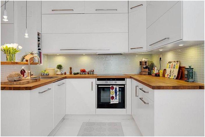 Светла U-образна кухня с дървен плот.