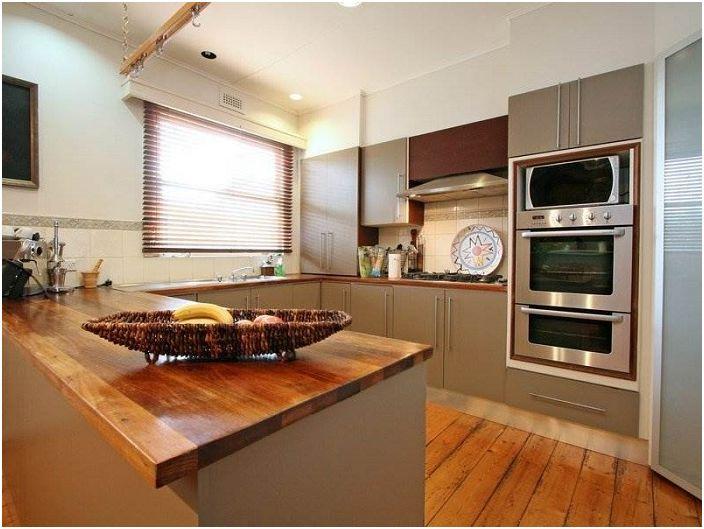U-образна кухня в сиви тонове с дървени елементи.