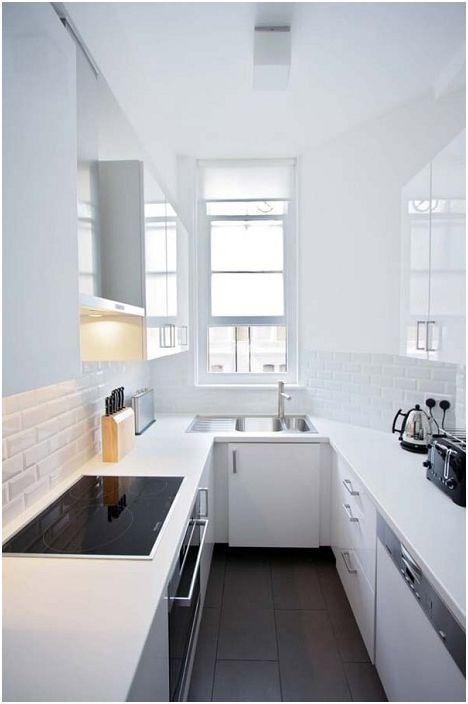 Valkoinen keittiö, jossa mustat palat, jotka näyttävät hyvältä.