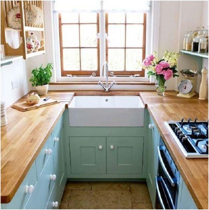 Oliivivärit U-muotoisen keittiön suunnittelussa, jossa on puinen työtaso.