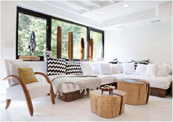 Dwa pnie drzew służą jako osobne stoły do dekoracji i uzupełnienia wnętrza.