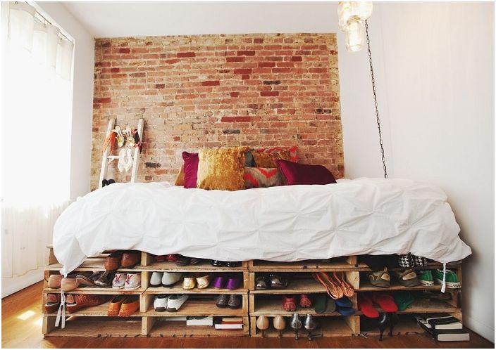Уютна малка спалня с палетно легло създава невероятна обстановка.