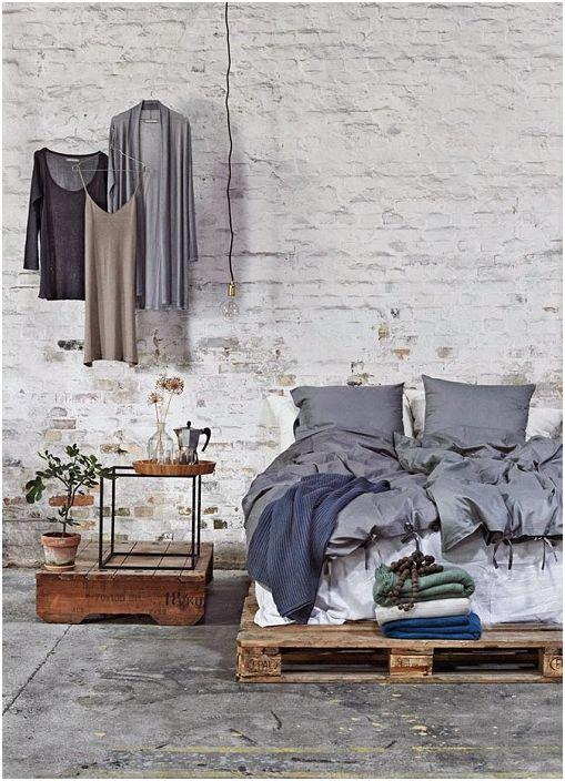 Суров индустриален таванско помещение с тухлени стени, циментен под и рамково легло с палети.