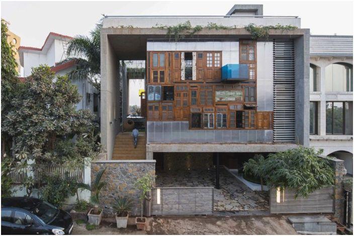 Къща с еклектична фасада, изработена от стари рамки и врати в Индия.