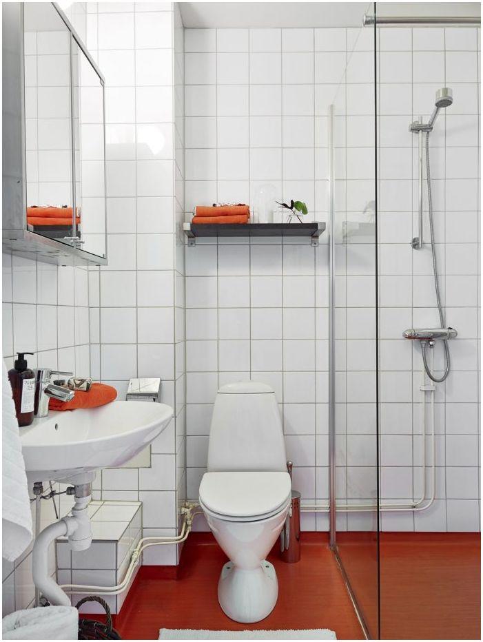 Ярко оранжеви елементи в интериора на банята в бяло