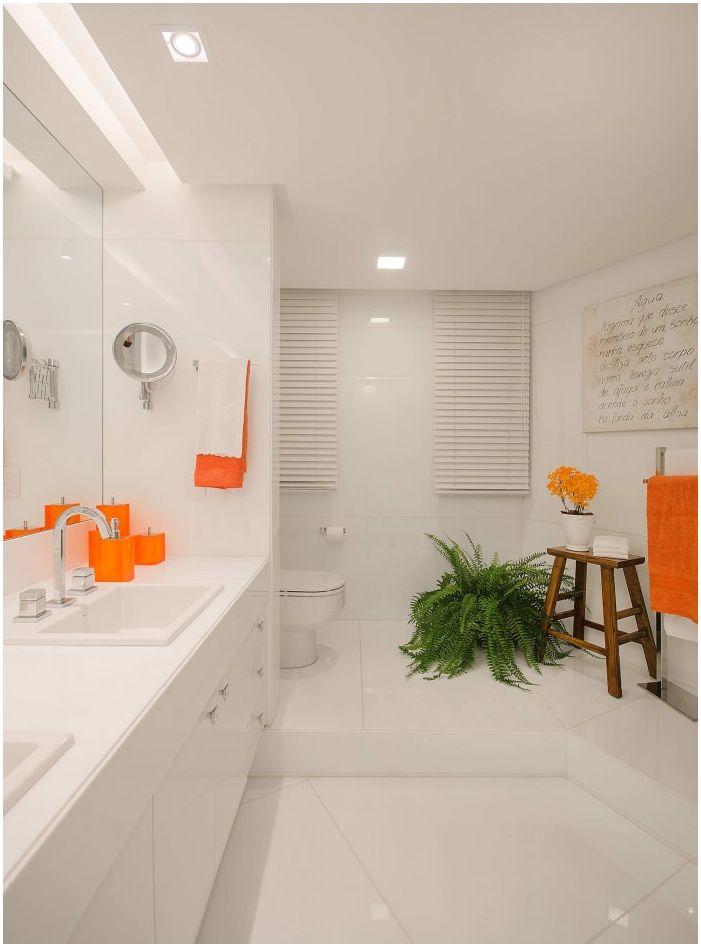Яркие оранжевые элементы в интерьере ванной в белом цвете