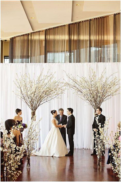 Креативно решение за използването на цъфтящи дървета и клони при декориране на сватбено тържество.
