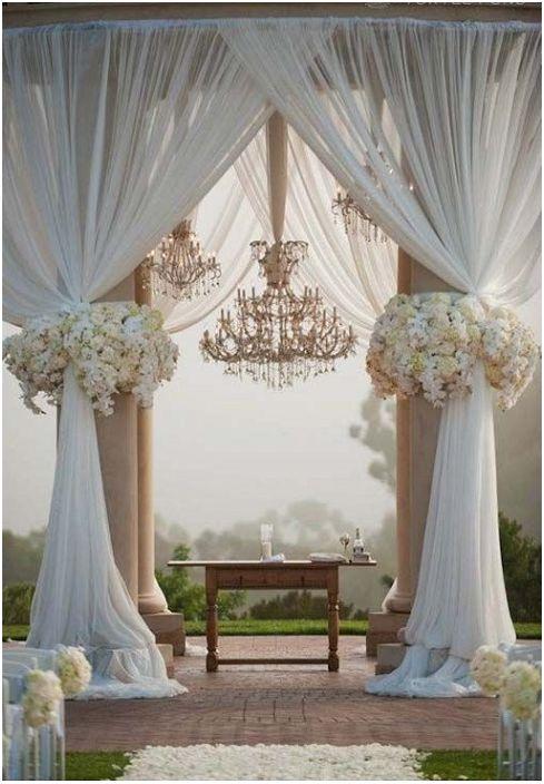 Красив дизайн на сватбена беседка със снежнобяли завеси, украсени с цветя.