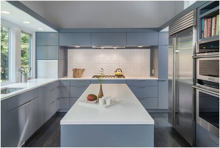 Yksinkertainen harmaa ja valkoinen keittiö mielenkiintoisella laattakuviolla.