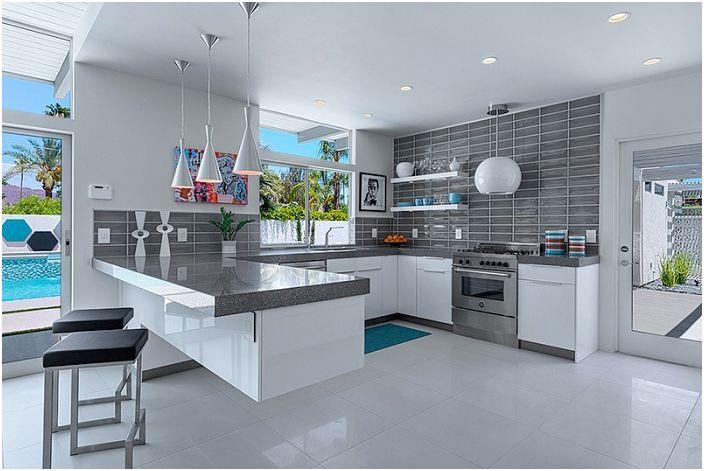Keittiön futuristinen muotoilu harmaissa sävyissä ilahduttaa silmää ja viehätää.