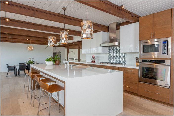 Keittiötila on sisustettu valkoisilla sävyillä, lisättynä puuta, mikä yksinkertaisesti ja täydellisesti korostaa tyylin erikoisuus.