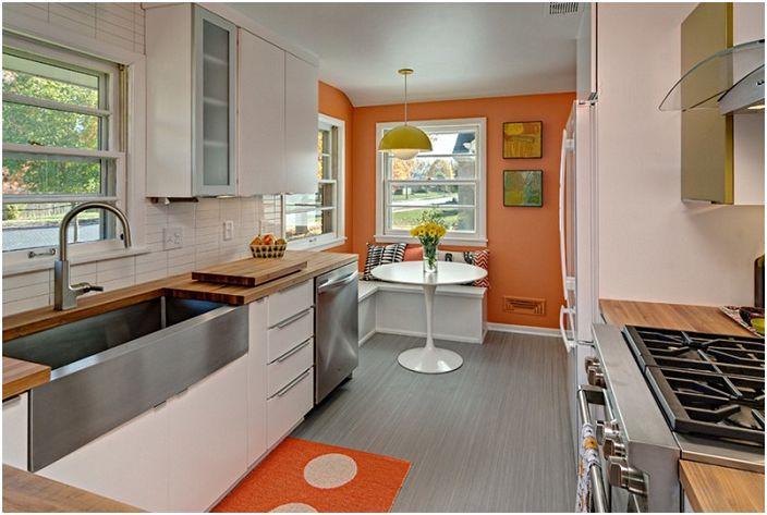 Keittiö, jossa on kirkkaan oranssi sisustus, joka lisää tilaa.