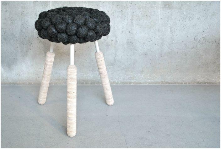 Taboret z tapicerowanym filcowym siedziskiem.
