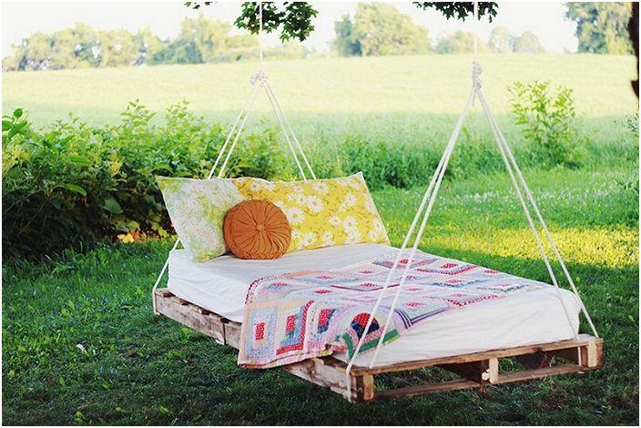 Wiszące łóżko wykonane z drewnianej palety. Ekonomiczna, stylowa opcja.