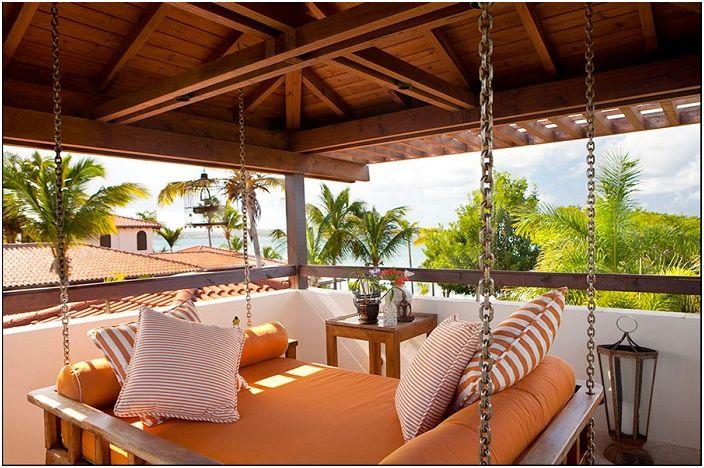 Ciekawy projekt wiszącego łóżka na świeżym powietrzu z przepięknym panoramicznym widokiem, który otwiera się z tarasu.