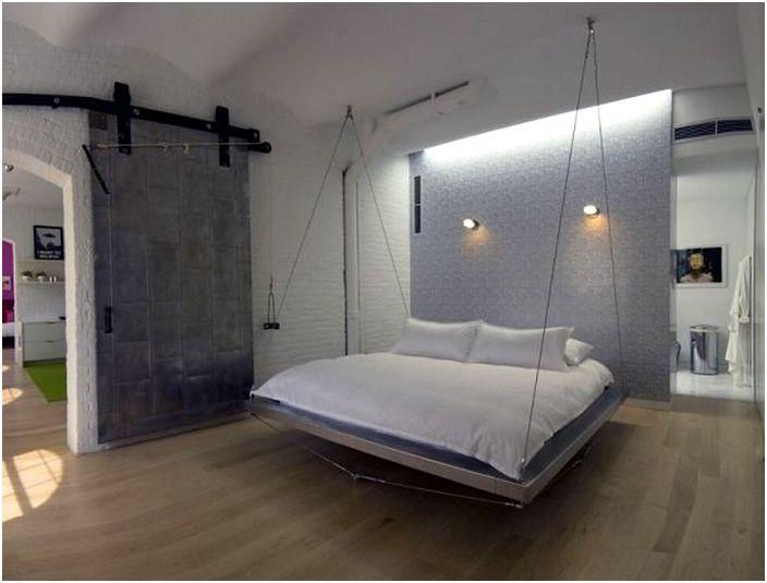 Прохладные серые цвета в спальне с подвесной кроватью.