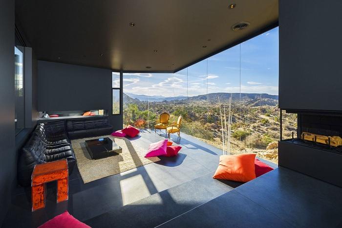 Интериорът на хола е направен в тъмни цветове за разлика от яркия панорамен акцент, който се отваря от прозореца.