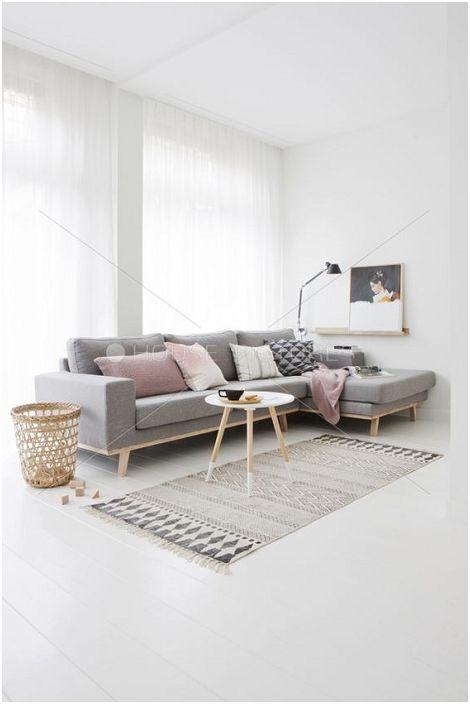 Nagyon szép, világos belső tér egy szürke kanapéval, amely kiemeli.