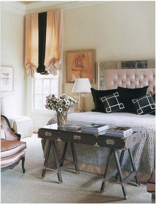 Ciekawe wnętrze sypialni uzupełnia stół u nóg łóżka, który zdobi wazon z kwiatami.