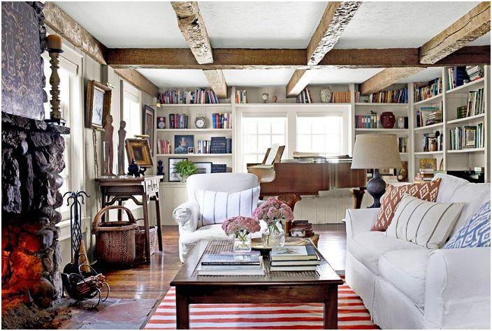 Ładne wnętrze salonu z jasnymi meblami i wyeksponowanymi belkami stropowymi.
