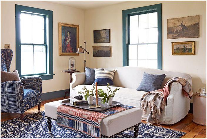 Ciekawy salon z niebieskimi oknami, ozdobiony obrazami.