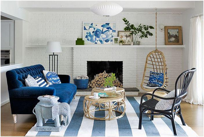 Salon z ultra niebieską sofą i białymi ceglanymi ścianami.