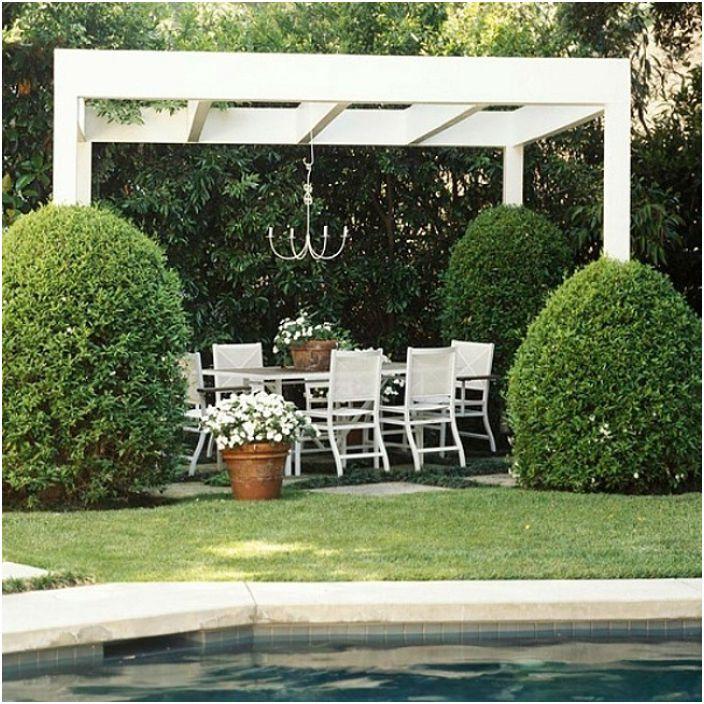 Винилова бяла беседка с кът за сядане до басейна, който защитава и акцентира върху заобикалящата зеленина.