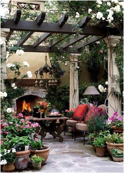 Страхотна идея за дизайн на пергола с каменни колони и дървен покрив, заобиколен от цветя, лозя, зеленина.