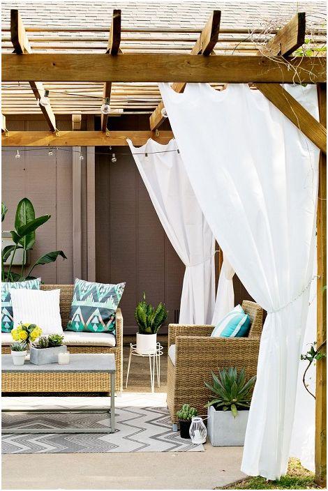 Мебелите допълват текстурите от дърво на обикновена беседка, докато завесите създават ефирна атмосфера.
