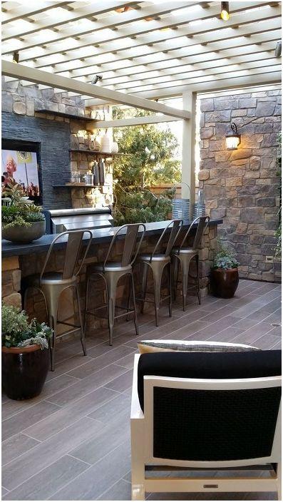 Отворената зона на бара е защитена от бяла беседка. Бар столове в индустриален стил подчертават зоната за сядане.