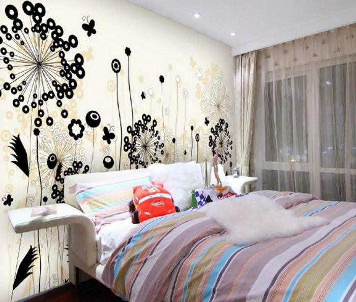 Ściana przy wezgłowiu łóżka ozdobiona jest naklejkami.