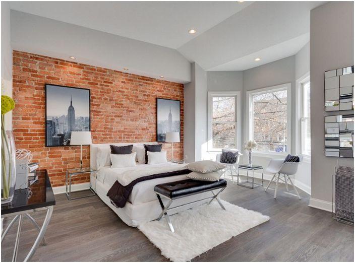 Комбинацията от твърди тухлени стени с мек бял килим е чудесна характеристика на стила на таванското помещение.