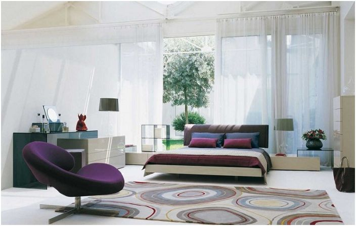 Спалнята е украсена с килим със сладки кръгчета и ярки възглавнички на дивана.