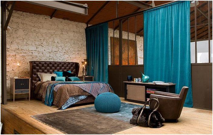 Хубава спалня с каменна стена и сини елементи в интериора.
