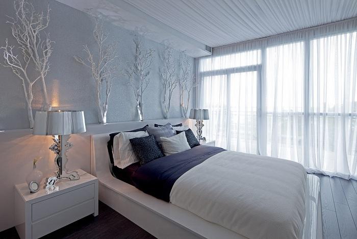 Спальня в светлых тонах удачно дополнена декорированными ветками, которые освежают общую обстановку.